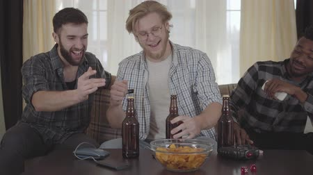 waar : Three young happy friends drinking beer and talking at home together