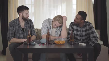 beer house : Two caucasian and one african american men sitting on the sofa. One guy has problem, two other soothe and cheer him up. Beer bottles and chips bowl are on the table. Old friends rest together