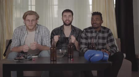 beer house : Two caucasian and one african american men resting together at home, watching boxing on TV. Beer bottles, empty chips bowl and boxing glove on the table Stock Footage