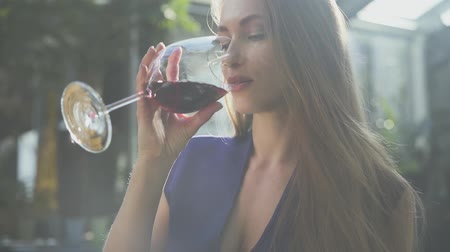 longo : Pretty elegant woman with long hair drinking red wine from the high glass in soft light. The lady is relaxed, she is smiling. Slow motion