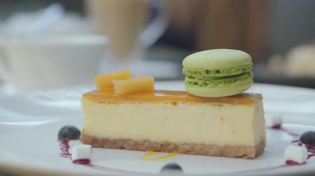 porce : Beautifully served tasty cheesecake with mango and berries and green macaron in restaurant. Close up