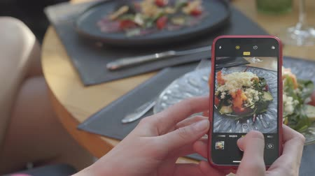mouth watering : Female hand taking photos on smartphone of fresh mouth-watering vegetables dish with decorations on the table. Stock Footage