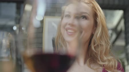 каберне : Portrait of pretty elegant blond woman with curly hair talking with friend in the background of blurred glass of red wine. The lady is relaxed, she is happy and smiling. Shooting through the glass