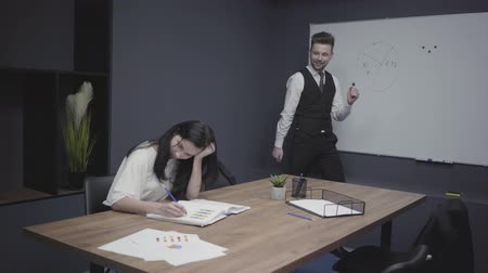 conference table : Young man is dancing near office board trying to cheer up his female colleague, who involved in work. Woman does not pay attention to guy and drawing in her notebook sitting at the table. Workplace