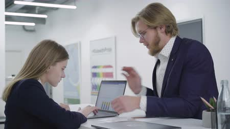 subordinate : Successful independent confident boss in a business suit flirting with a subordinate or secretary. Handsome bearded director wearing glasses shakes hands with a beautiful girl. Workplace. Office space.