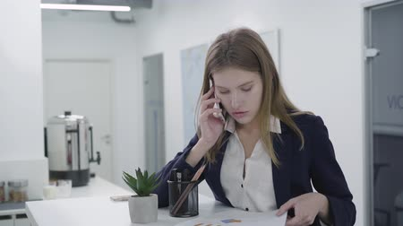 educado : Concerned young lady in formal dress talking by cellphone checking papers in the office standing at the counter. Woman with long hair solving problems. Workplace. Office space.
