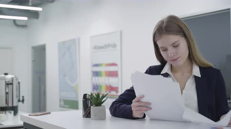 začít : Concerned young lady in formal clothes attentively checking papers in the office standing at the counter. Woman with long hair solving problem. Workplace. Office space.