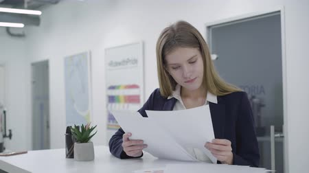 concerned girl : Thoughtful young lady in formal clothes attentively checking documents in the office standing at the counter. Woman with long hair surprised at what is written on paper. Workplace. Office space.