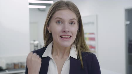 evet : Portrait of a contented, happy, satisfied secretary or businesswoman in a business tight suit looking at the camera and showing her positive emotions. Workplace. Office space.