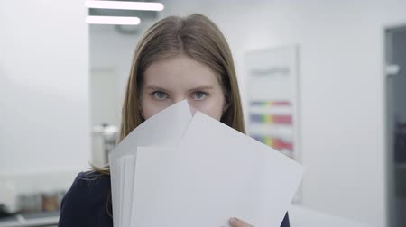 evet : Portrait of cute playful young lady in formal clothes hiding her face behind papers looking in camera and away. Woman with long hair have fun in the office