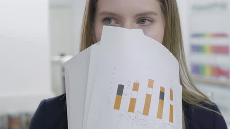 ワークステーション : Close up portrait of cute playful young lady in formal clothes hiding her face behind papers looking in camera and away. Woman with long hair have fun in the office