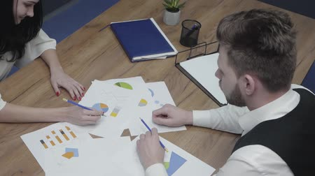 diagrama circular : Young man and woman sitting at the table in the office. Colleagues discussing charts and schemas depicted on paper. Co-workers came to a consensus and shake hands. Shooting from above, top view Archivo de Video