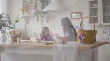 easter : Cute mother and her pre teen daughter arguing on the kitchen. Woman explaining to the girl the reasons, but stubborn daughter defends her opinion. Relationship mothers and daughters. A happy family. Stock Footage