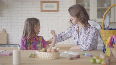 coloração : Young mother and her preteen daughter talking on the kitchen. Woman listening to her emotional girl, telling her story with angry face showing fist. Easter eggs are on the table. Camera moves right