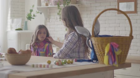 easter : Young mother and her preteen daughter talking on the kitchen. Woman listening to her emotional girl, caress her hair and shoulder. Easter eggs are on the table. Relationship mothers and daughters. Stock Footage