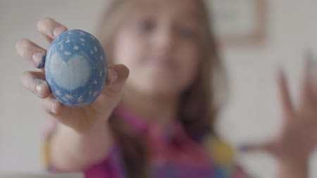 boiled egg : Cute little girl holding blue easter egg with painted heart in hand, showing it to camera. The focus moves from the Easter egg to the girl. Concept of creativity, traditions. Preparation of the Easter Stock Footage