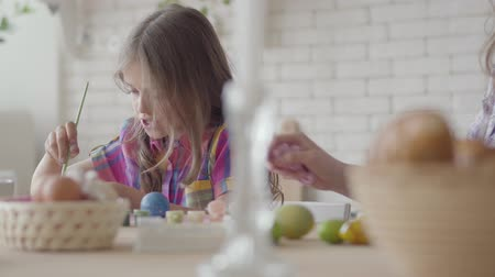 easter : Woman and little girl coloring easter eggs with colors and brush. Preparation for Easter holiday. A happy family. Stock Footage