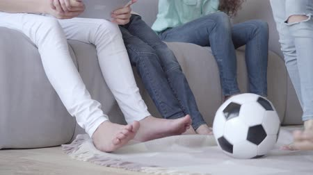четверть : Closeup of legs of mother and her sons. Woman and three boys in jeans sitting on the couch sofa near each other. Fourth boy comes and sits near. Happy big cheerful loving family