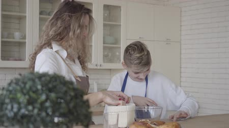 bun : Pretty woman and her teen son cooking cake in the kitchen, the boy helping mother to make food. Mom trying to stain the face of kid with flour, both people smiling. Happy family have fun at home