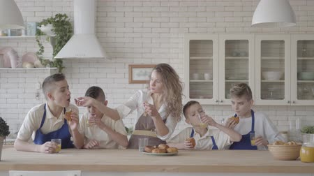 despreocupado : Portrait attractive happy woman and her four teen son eating pies and drinking orange juice in the kitcken standing at the table. Everybody wearing aprons. Kids helping mother to cook food