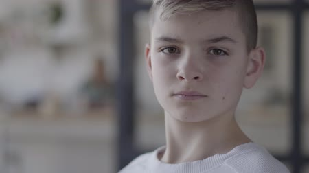 carelessness : Close up portrait of a young boy looking in camera. The emotionless boy in a white t-shirt. Real people. Stock Footage