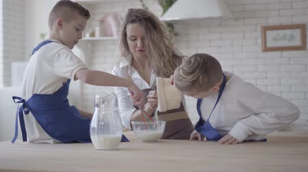 ジュニア : Pretty woman and her two sons cooking making dough in the kitchen, the boys helping mother to make food. Mom pouring flour in the bowl and kid mixing it. Happy friendly family 動画素材