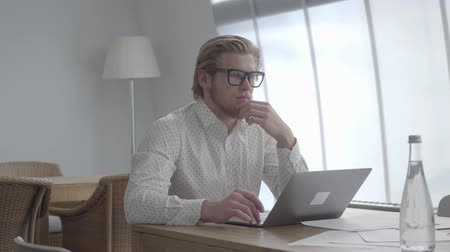 ネットブック : Blond thoughtful man in glasses sitting at the table in a light comfortable office in front of netbook. Handsome businessman stroking his beard thinking about work.