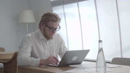 sobre : Confident blond thoughtful man in glasses sitting at the table in a light comfortable office in front of netbook. Handsome businessman stroking his beard thinking about work.