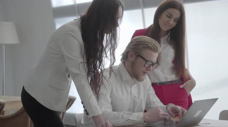 explicando : Blond man in glasses sitting in a light comfortable office with netbook at the table explaining his idea to colleagues. Two girls in formal wear standing near listening to boss. Vídeos
