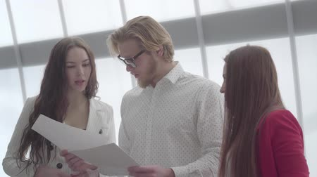 zasedací místnost : Portrait successful blond man in glasses explaining his idea to two female colleagues standing on either side of him in a light comfortable office. Two girls in formal wear listening to boss