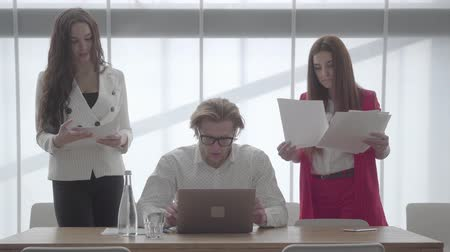 netbook : Portrait blond man in glasses sitting in a light comfortable office with netbook. Two girls in formal wear with papers standing on either side of the boss.