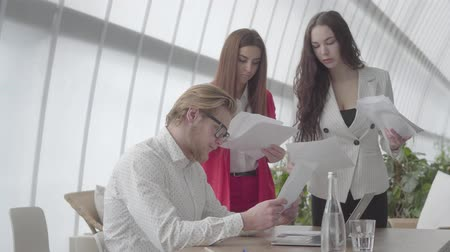 netbook : Portrait tired businessman sitting in a comfortable office with netbook at the table examining documents which female colleagues gives to him one by one. Two girls in formal wear standing on either side of the boss