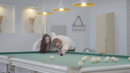 sinuca : Successful blond bearded man teaches his girlfriend to play billiard. Confident man in white shirt explains to the woman in elegant suit how to play pool. Billiard sport concept Stock Footage
