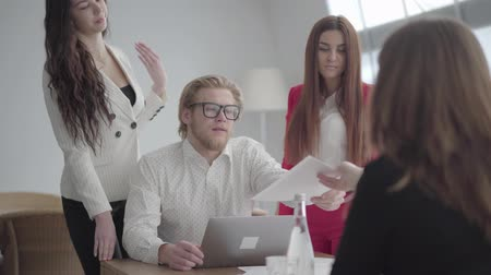 netbook : Blond man in glasses sitting in a light comfortable office with netbook at the table. Two girls in formal wear standing near and one sitting in front of him, giving documents to the boss. Working process