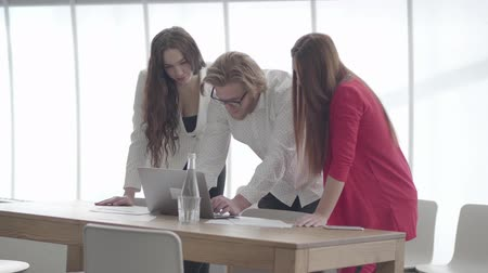 ohnutý : Handsome blond man in glasses bent over netbook in a light comfortable office showing information to female colleagues. Two women in formal wear standing on either side of the boss