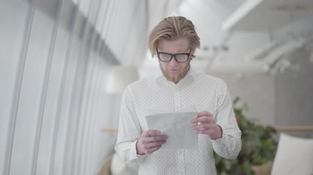 役員室 : Portrait successful blond man in glasses standing in a light comfortable office reading papers. Handsome businessman involved in his work. Workplace. Office space.