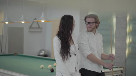 sinuca : Blond bearded man and his girlfriend talking near the billiard table. Confident man in white shirt explains to the woman in elegant suit how to play pool. Billiard sport concept. Man and woman flirting