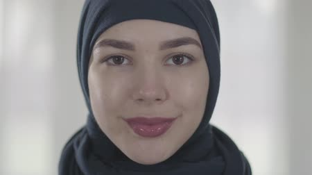 frizura : Portrait of a young smiling eastern woman in the modern Muslim clothes and beautiful black headdress close up. Young asian Muslim woman in head scarf looking in camera Stock mozgókép