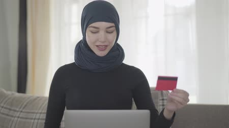 frizura : Young smiling eastern woman in the modern Muslim clothes and beautiful headdress using a credit card to pay online using laptop. Young asian Muslim woman in headscarf buying items in the internet shop Stock mozgókép