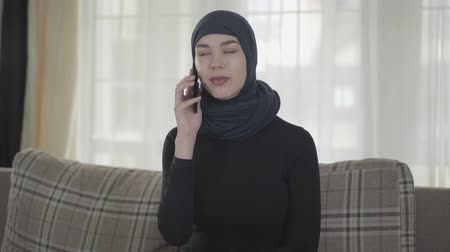 головной платок : Portrait of independent serious young muslim woman talking by smartphone wearing traditional headscarf