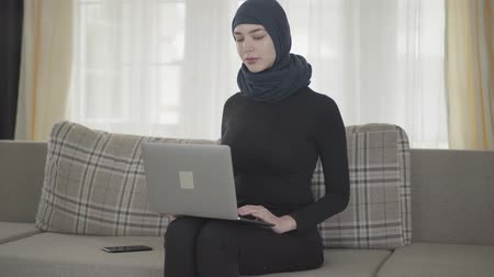frizura : Portrait young smiling successful confident girl in balck clothes and beautiful headdress working with her laptop sitting on the sofa at home. Young asian Muslim woman in headscarf surfing the web