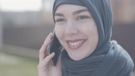 frizura : Close up portrait of a young beautiful muslim woman in black headdress talking by cell phone close up. Cute asian girl in head scarf looking in camera.
