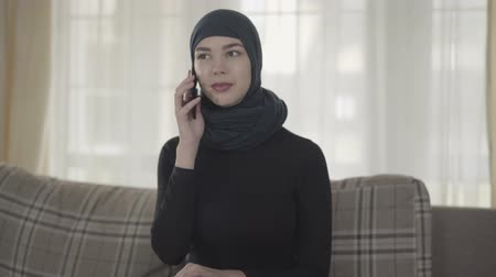 frizura : Portrait of a young beautiful muslim woman in black headdress talking by cell phone indoors. Cute asian girl in head scarf looking in camera