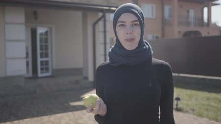 frizura : Young smiling eastern woman in the modern Muslim clothes and beautiful black headdress standing in front of a big house eating apple. Asian woman in headscarf near her home, front view