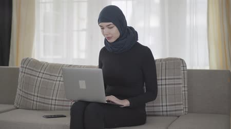 frizura : Successful confident girl in balck clothes and beautiful headdress working with her laptop sitting on the sofa at home. Young asian Muslim woman in headscarf surfing the web