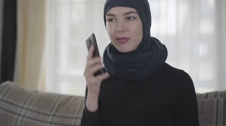 frizura : Young beautiful eastern woman in the black clothes and beautiful headdress calling by cell phone. Young asian Muslim lady in head scarf using gadget sitting on the sofa at home looking on camera