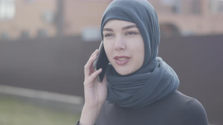 frizura : Portrait of a young eastern woman in black clothes and beautiful headdress talking by cellphone close up. Asian woman in headscarf bought a new home. Stock mozgókép