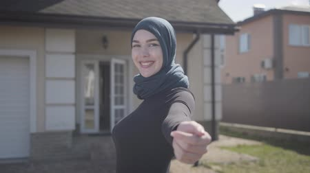привлекать : Portrait of independent young muslim woman smiling and flirting wearing traditional headscarf on the background of house