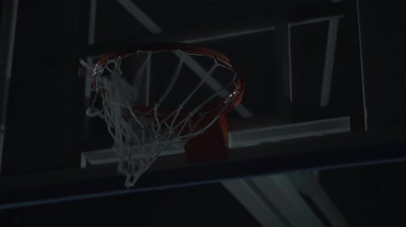 basketbal : Close up image of professional basketball player making slam dunk during basketball game in dark basketball court. Stockvideo