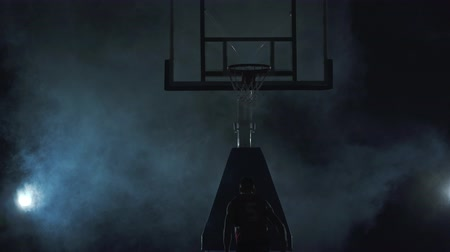altura : Young basketball player in red uniform throws the ball in the basket on the dark background in the cloud of smoke. Professional basketball game player in action. Concept of sport Stock Footage